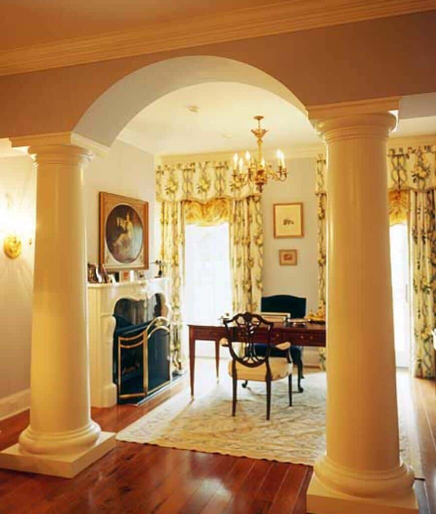 Warm home office lined with huge columns forming an archway offers a cozy area rug and elegant fireplace covered with brass screen. It has wood plank flooring and glazed windows dressed in lovely draperies and valences.