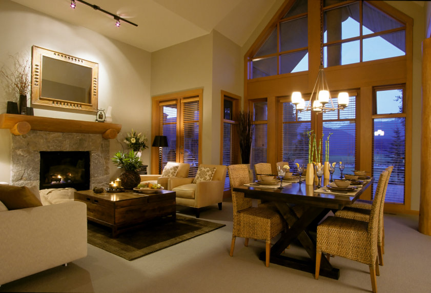 This great room offers a very elegant living room set near the fireplace and a romantic dining table set lighted by a gorgeous modern chandelier.