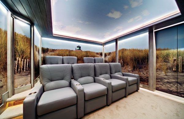 This home theater boasts a very attractive wall and ceiling theme. The room also features comfortable sectional seats.