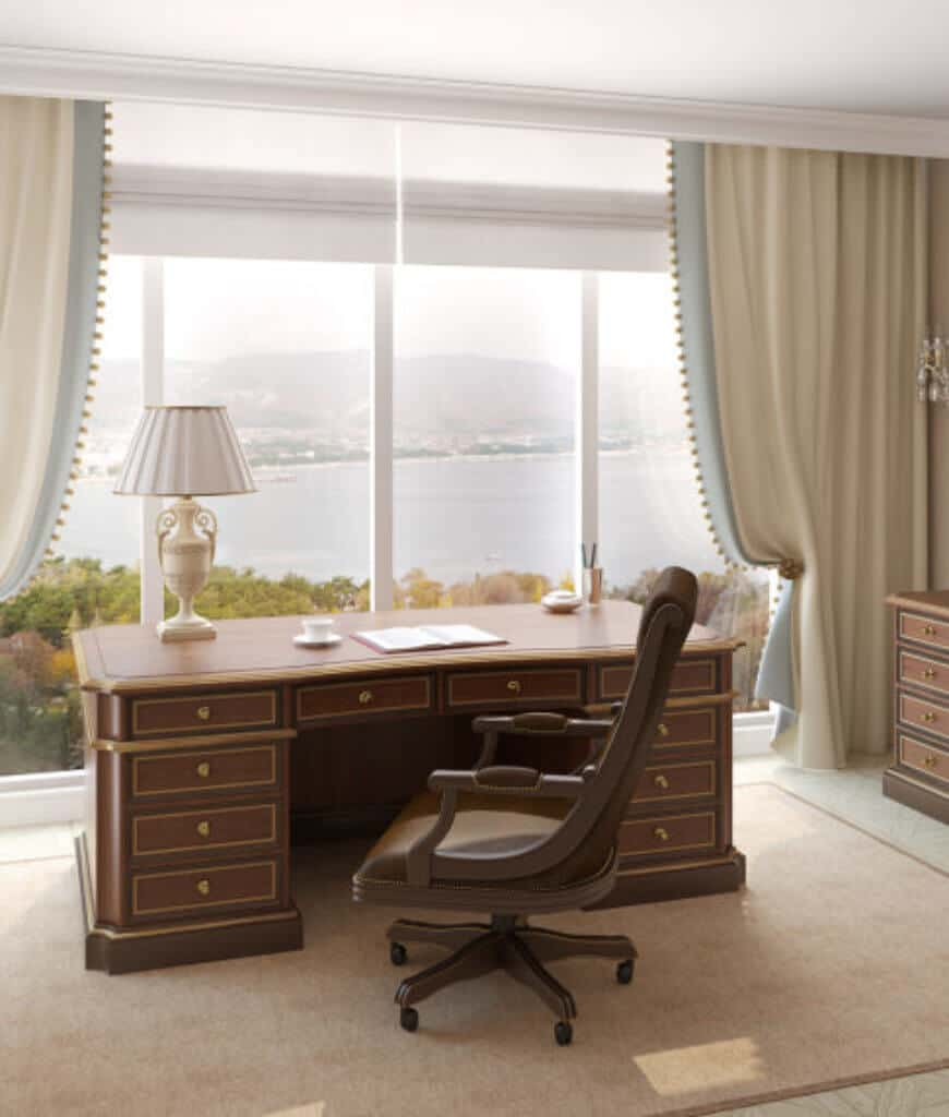 This home office boasts a wooden desk topped with a white table lamp and brown swivel chair on a beige rug. It also has a panoramic window overlooking a breathtaking view.