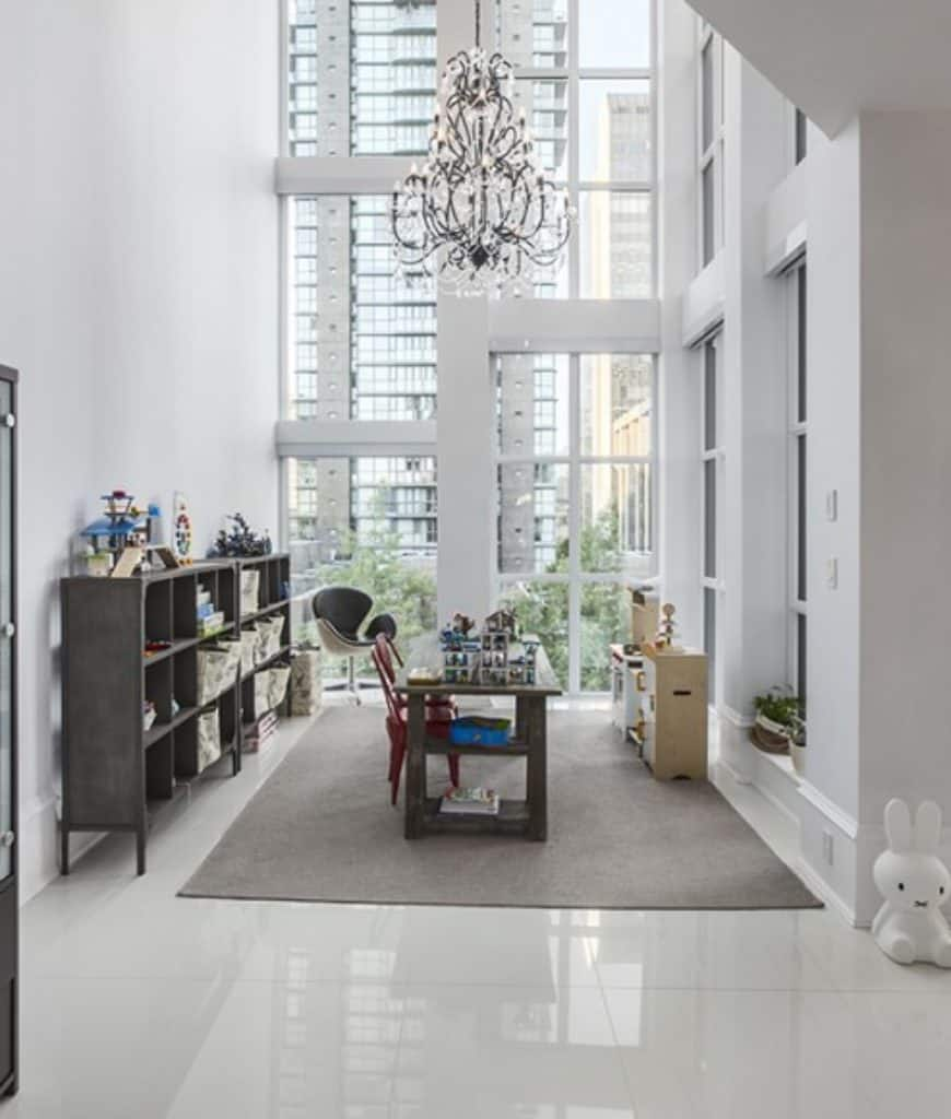 Luxury home office with full height glazing and tiled flooring topped by a gray area rug. It is illuminated by a glamorous chandelier that hung from the high ceiling.
