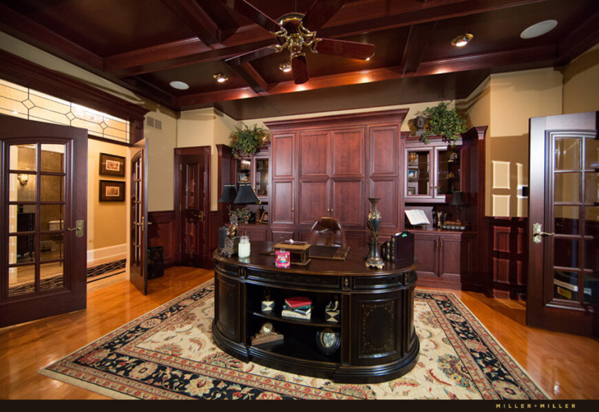 Large home office with an elegant office desk set on a handsome rug. The coffered ceiling adds elegance to the room.