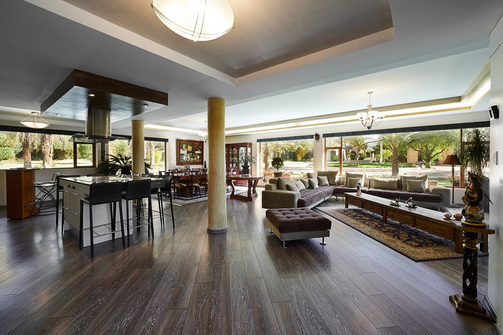 Large great room featuring hardwood flooring and stylish ceiling, along with a modish set of sofa and a classy set of dining table and seats.