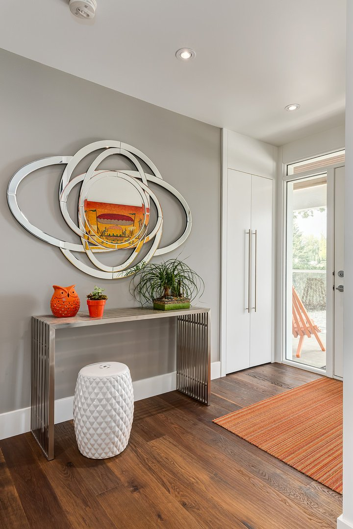 A statement mirror hung over a metal bar console table paired with white textured stool in this foyer. Orange color pops out from the decors, striped rug and canvas painting that's being reflected on the mirror.