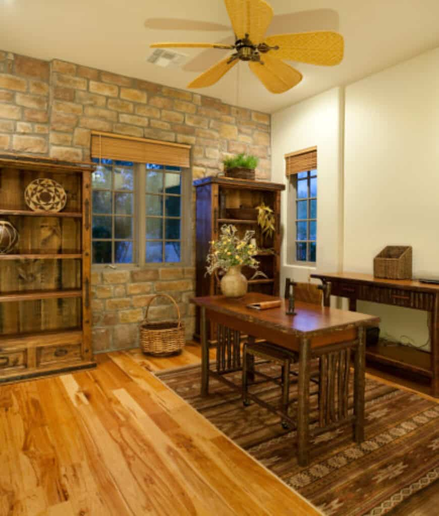 Rustic home office offers open shelving along with a wooden desk and chair that sits on a brown area rug over hardwood flooring. It includes brick accent wall and framed windows covered with wicker roller blinds.