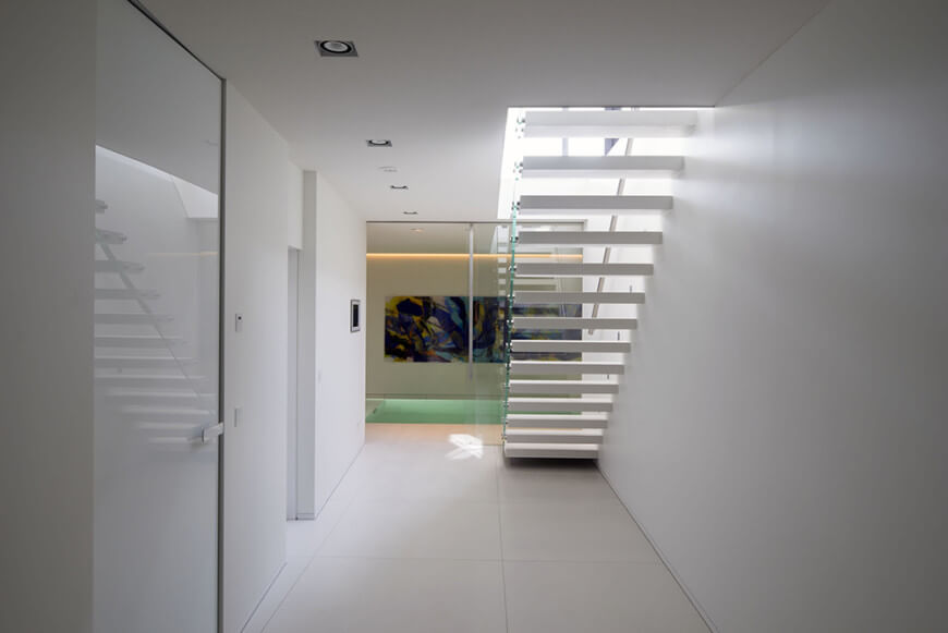 A contemporary staircase along the white hallway with open riser and white treads framed with glass railing.