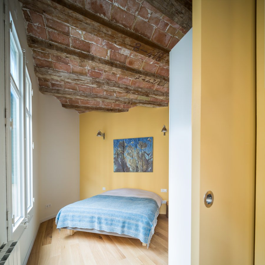 Primary bedroom showcases a brick ceiling with exposed wood beams along with hardwood flooring, It has a wall art canvas on a yellow wall placed above the blue bed.