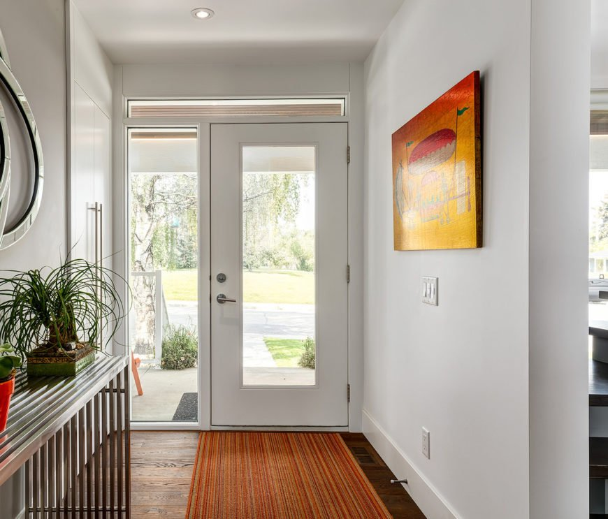 A closer look at this foyer's white front door with glass panels overlooking the outdoor view.  There's a built-in storage cabinet adjacent to it that faces the canvas painting.