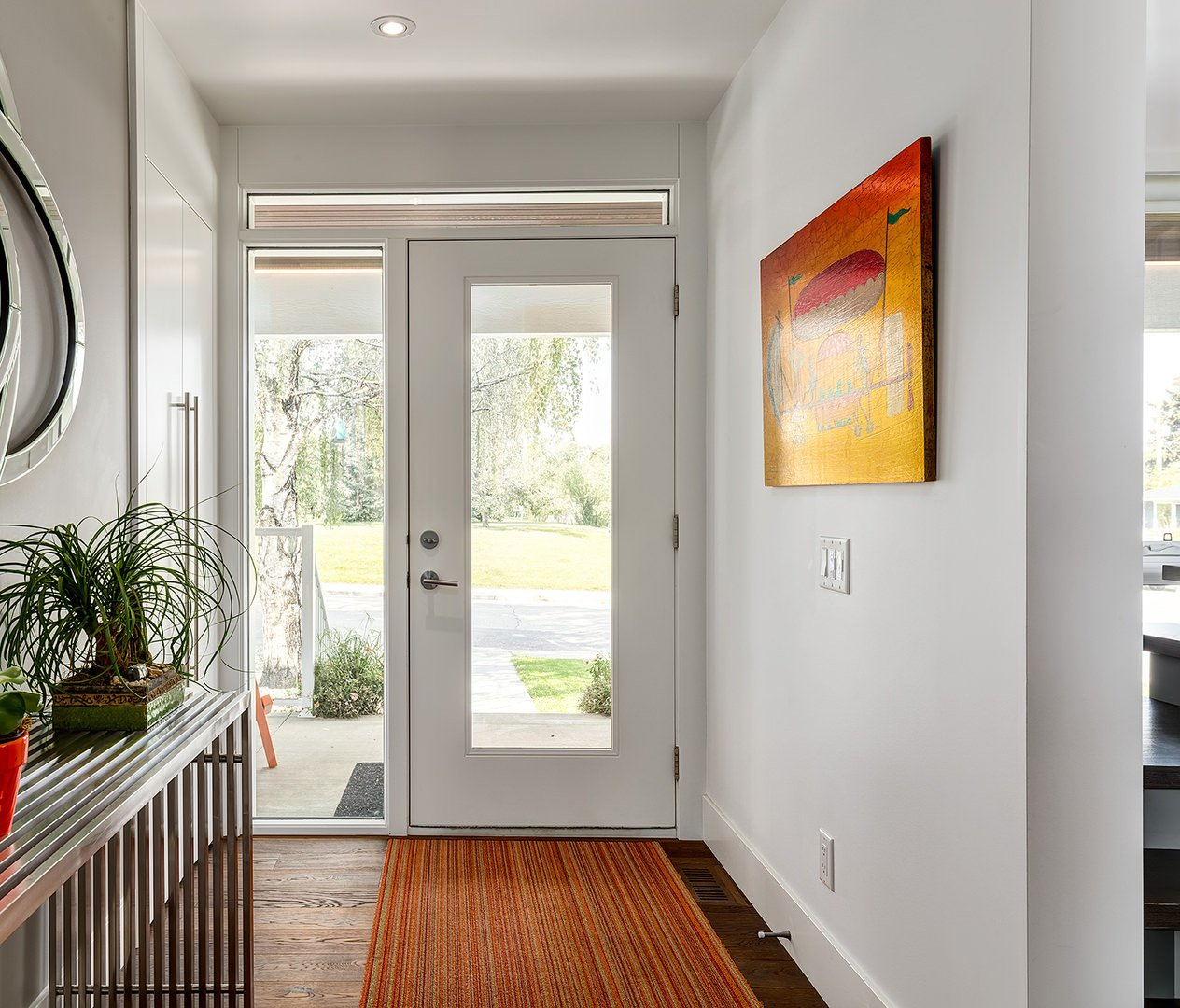 Small bright foyer with white walls featuring an artistic wall art. The flooring with a rug looks perfect with the hallway's style.