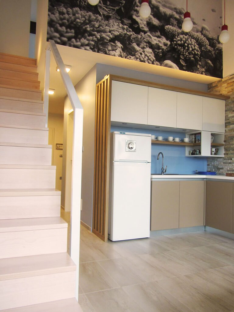 A small kitchen decorated with a black and white coral reef wall art mounted above the white cabinetry and fridge. It has a wooden floating shelf fixed to the light blue backsplash that complements with the brown lower cabinetry.