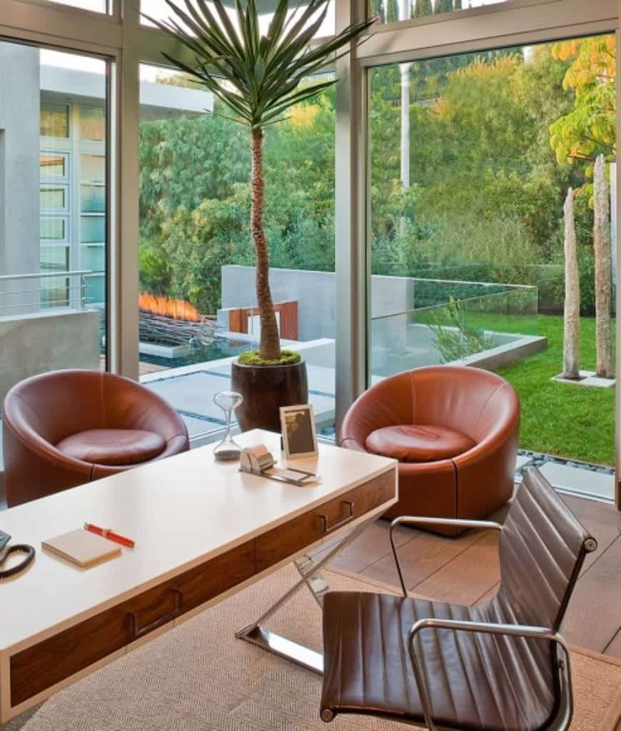 Fresh home office features wide plank flooring and full height glazing with a clear view of the serene outdoor greenery. It has a wooden desk and brown leather chair over a jute rug accompanied by coral round back chairs.