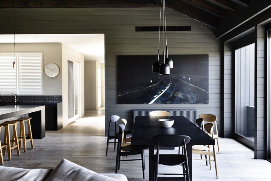 Dark dining area with a huge black canvas mounted on a gray shiplap wall. It features a black dining table with chairs mixed of wood and black color.