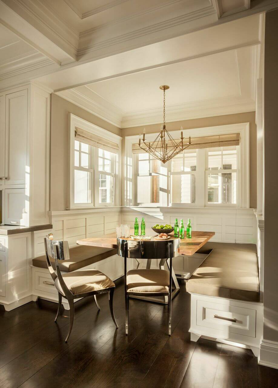 Classic dining nook fitted in the corner with white shiplap walls and wide wood plank flooring. It has a wooden dining table surrounded with U-shaped built-in seating and a pair of stylish mirrored chairs.