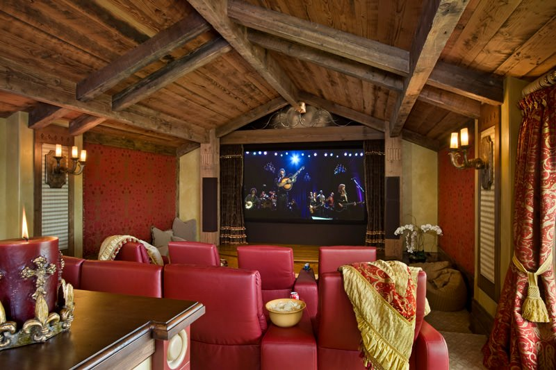 A rustic style home theater featuring classy walls and vaulted ceiling with exposed beams together with a modish set of theater seats.