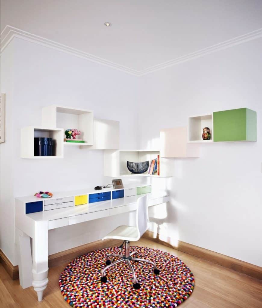 Minimalist home office with floating shelves and a built-in desk fitted with multicolored drawers and paired with a sleek white chair that sits on an eye-catching round rug.