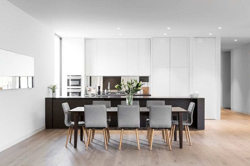 A long black kitchen bar stands out from this elegant white kitchen. It has tall white cabinets, stainless steel double ovens, recessed lighting and a dining table with gray chairs.