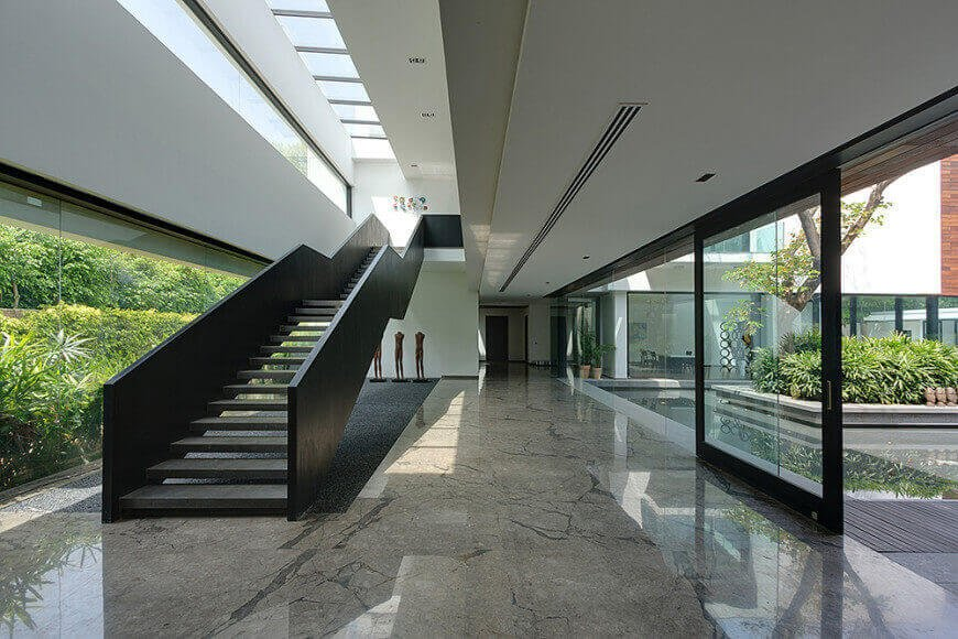 The airy glazed house boasts an elegant marble flooring and a black straight staircase with mid landing.