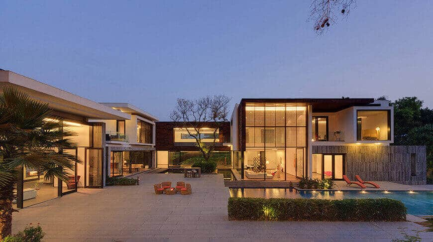 Modern mansion boasting a large swimming pool along with a patio area and a fire pit.