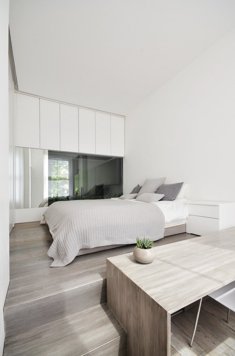 A minimalist primary bedroom boasts a wooden platform bed with storage and a desk. It is surrounded by plain white walls and cabinets.