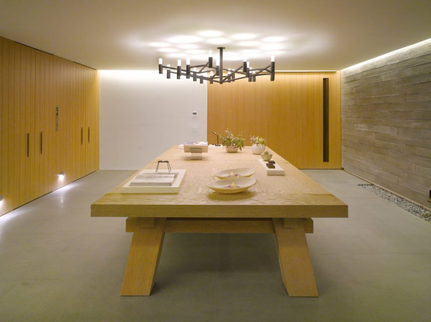 This dining room boasts a huge wooden table that complements with the mustard yellow shiplap wall and storage. It is lighted by an oversized chandelier that hung from the low white ceiling.