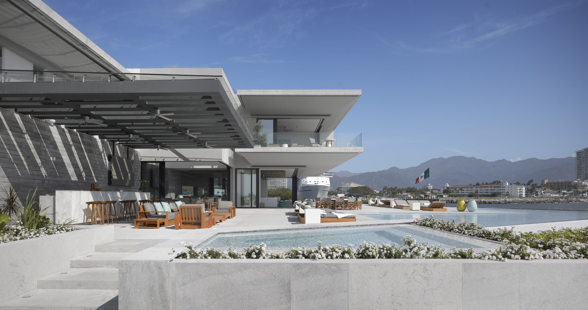 Huge modern house featuring a large patio and lounging area. There's also a bar and outdoor kitchen behind the patio area.