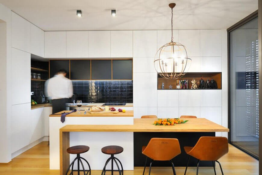L-shaped white minimalist eat-in kitchen with knobless white cabinets, dark tile backsplash, and a globe candelabra chandelier above the tiny dining area attached to the kitchen island with wood surface.