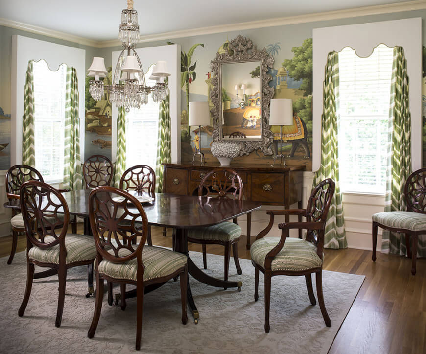 Fabulous dining room features wood plank flooring topped by a floral textured rug along with louvered windows covered with green chevron curtains.