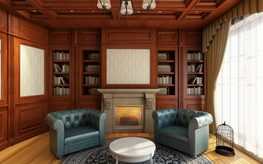 A classy home library with built-in bookshelves and a fireplace along with elegant blue seats set on the hardwood flooring topped by a handsome rug.