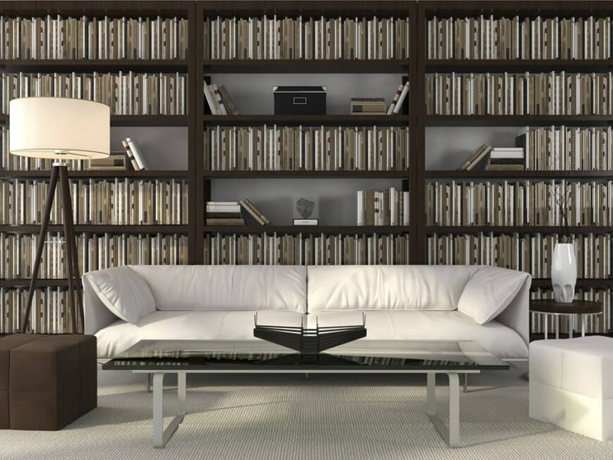 A home library with massive bookshelves and white cozy couch along with a long glass top center table set on the carpet flooring.