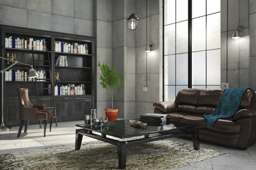 This home library features stylish black bookshelves and gray walls along with a stylish center table and a leather couch.