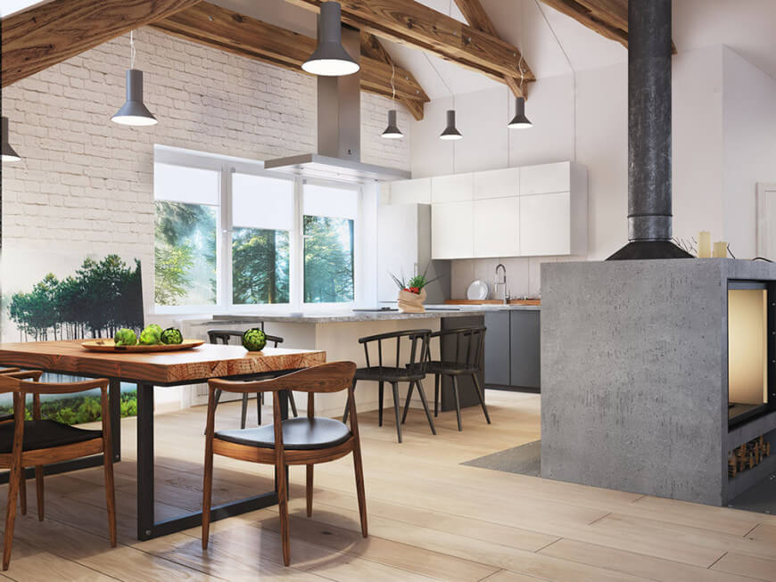 An open kitchen features a double sided concrete fireplace that faces the white breakfast island with marble countertop and round back chairs. It has light wood plank flooring and cathedral ceiling framed with wood beams.