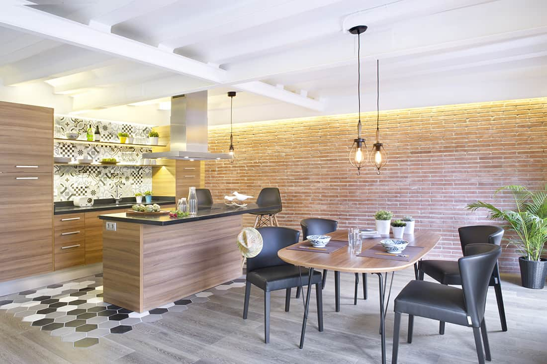 Large industrial kitchen with a brick wall, hardwood flooring and black countertops on both kitchen counter and center island. The warm white lights make this kitchen look romantic.
