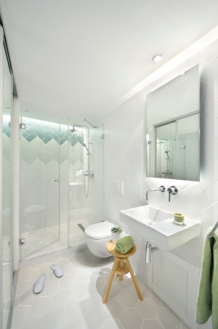 Quaint and simple blend together seamlessly in this simple but neat and comfortable bathroom. Clear glass paneling encloses the generously sized walk in shower and light grey hexagonal tiling covering the floor adds a bit of lively detail.