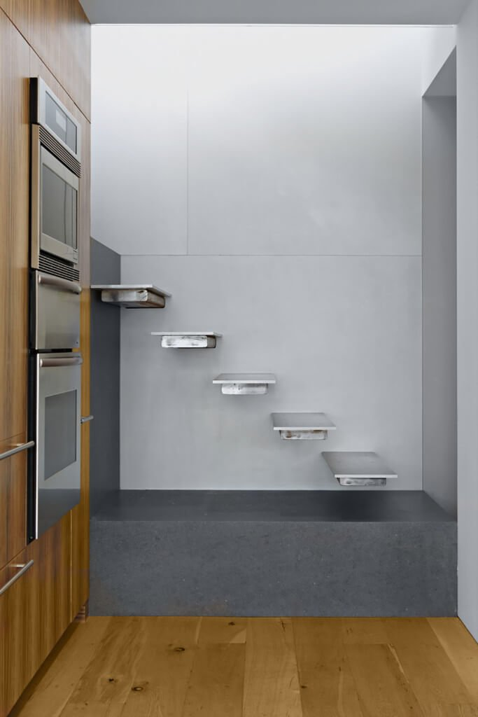 Sleek staircase showcases dark gray concrete landing and modern metal treads fixed to the light gray wall.
