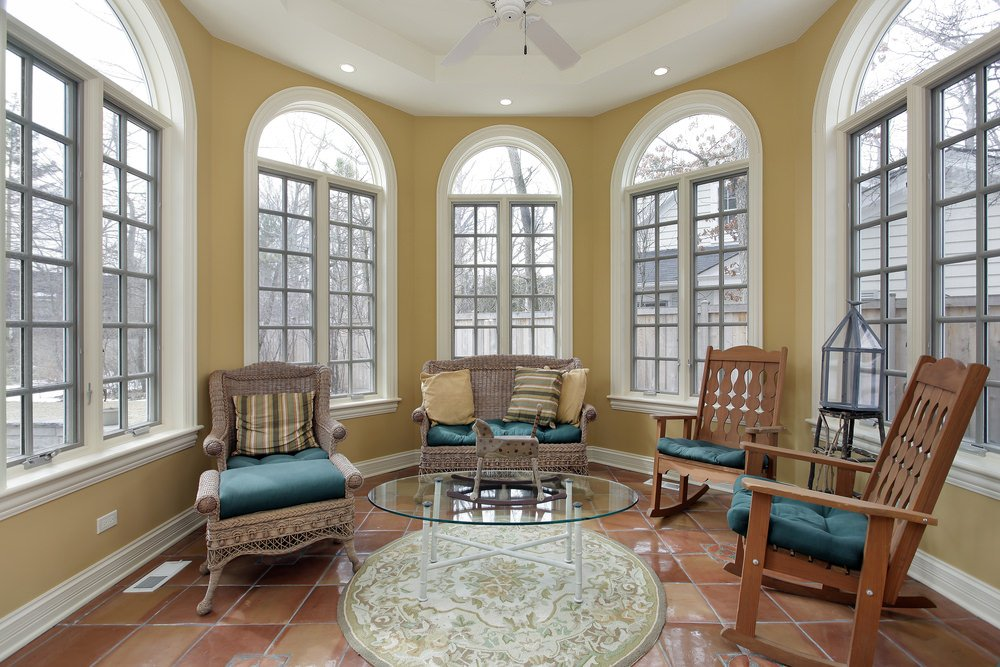 A tiled sunroom with a decorative rug, traditional chairs and a glass top table.