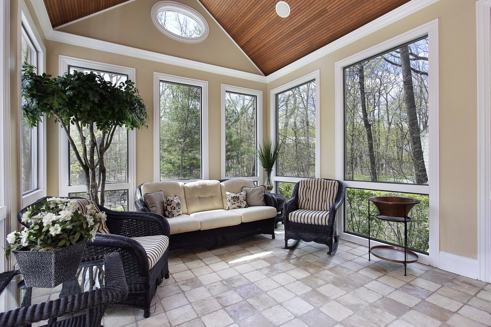 A country-style sunroom with tiled floor, glass windows and some potted plants.