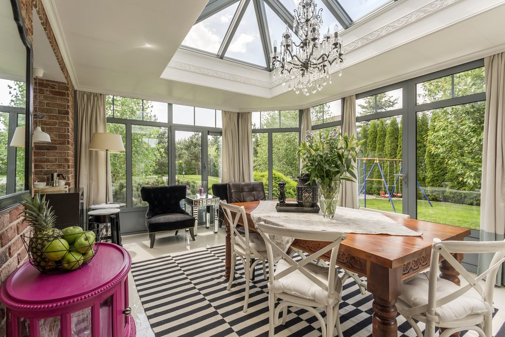An eclectic sunroom with a garden view. The walls are made up of bricks and the floor is covered with a creative, striped carpet.