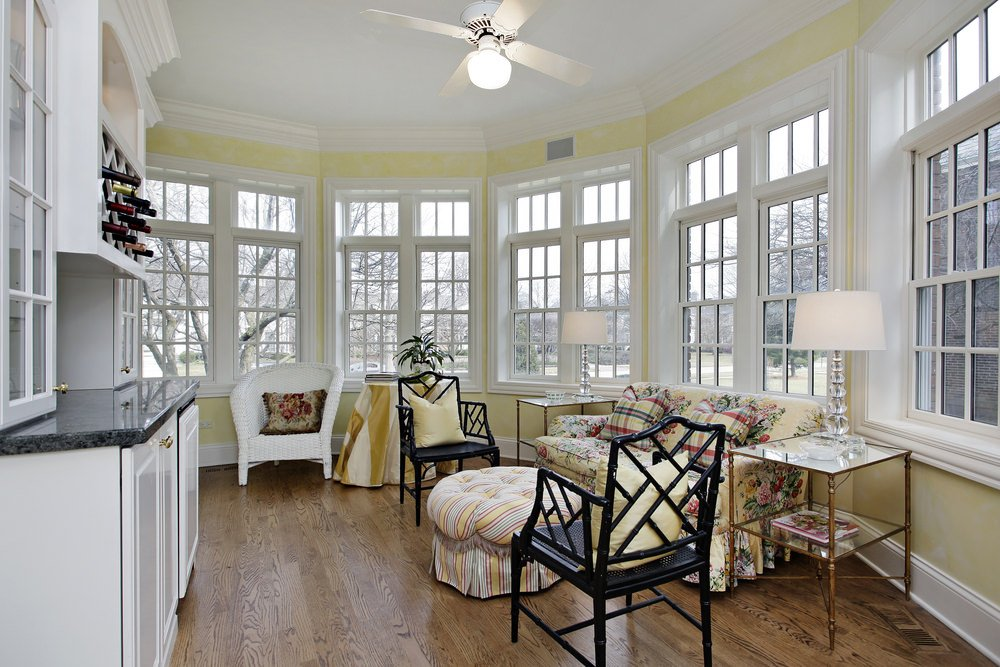 Country-style sunroom with hardwood floor and a floral couch.