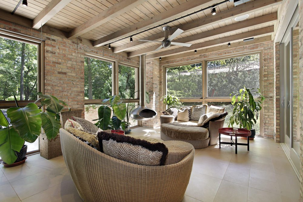 A tropical type of sunroom incorporated with some detailed chairs, bricked walls, tiled floor and of course, some potted tropical plants.