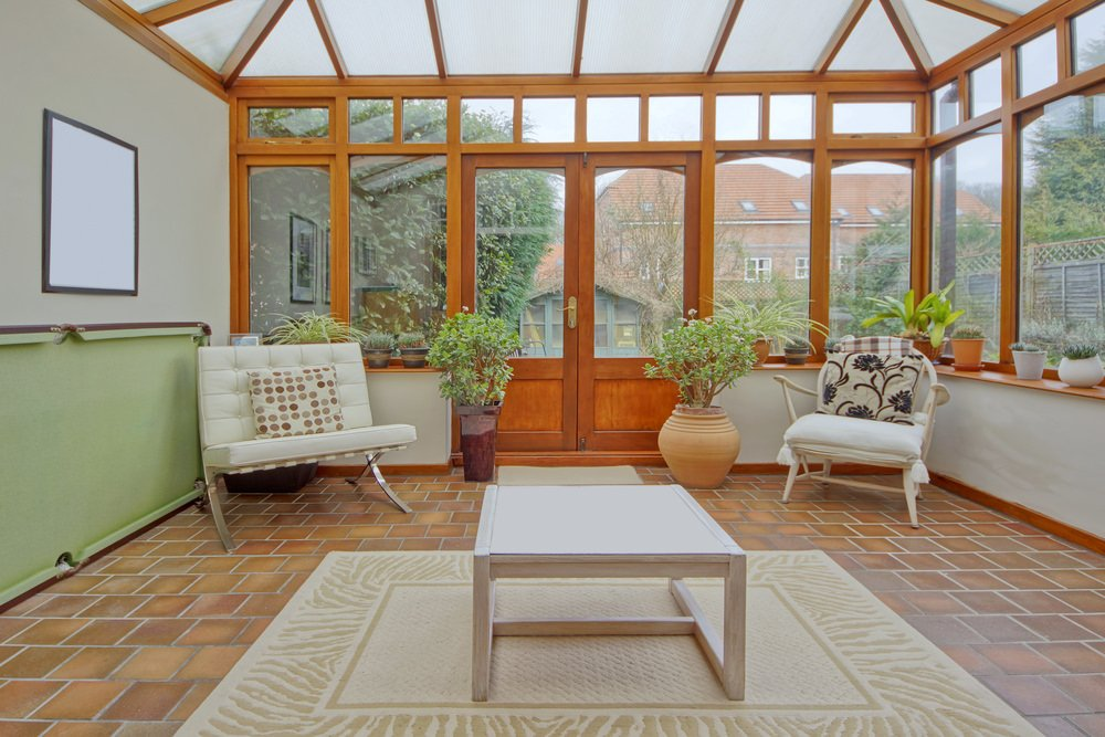 A country-style, tiled sunroom dominated with warm tones of brown and orange.