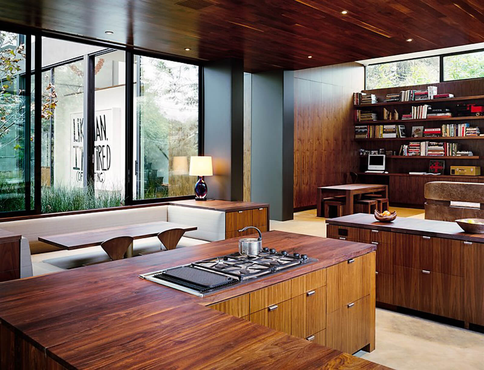 An all wood kitchen with a dining nook by the glass window offering a built-in seating fitted with white leather cushions and wooden dining table with matching chairs.