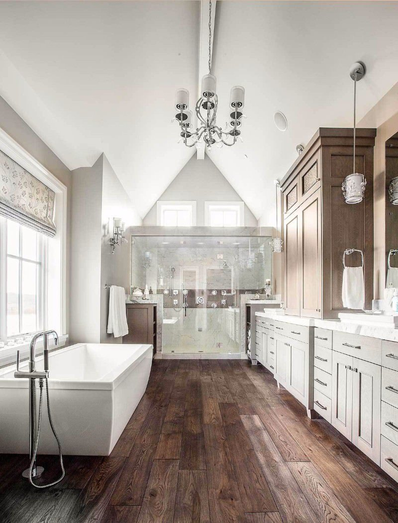 Craftsman bathroom with lengthy sink vanity and freestanding bathtub over wood plank flooring. It is lighted by a chrome chandelier that hung from the cathedral ceiling.
