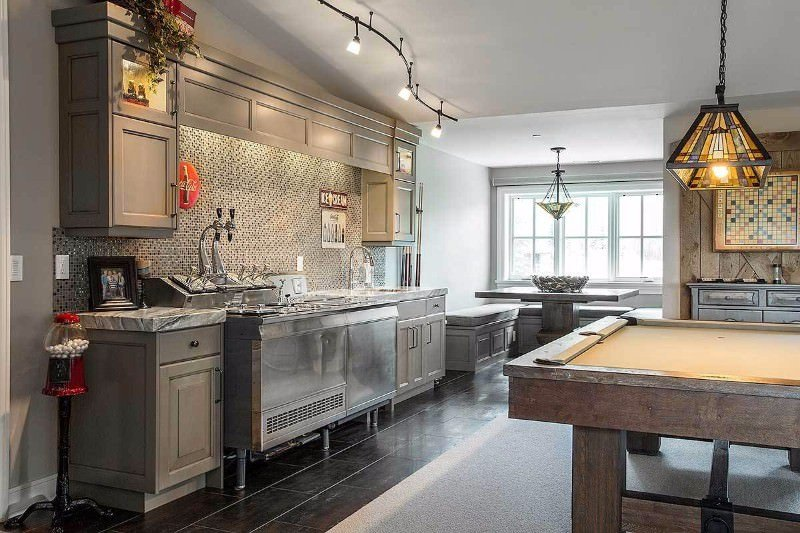 This kitchen offers a dining nook on the side along with a billiards table on the center. The single wall style is lighted by track lights and cabinetry lighting.