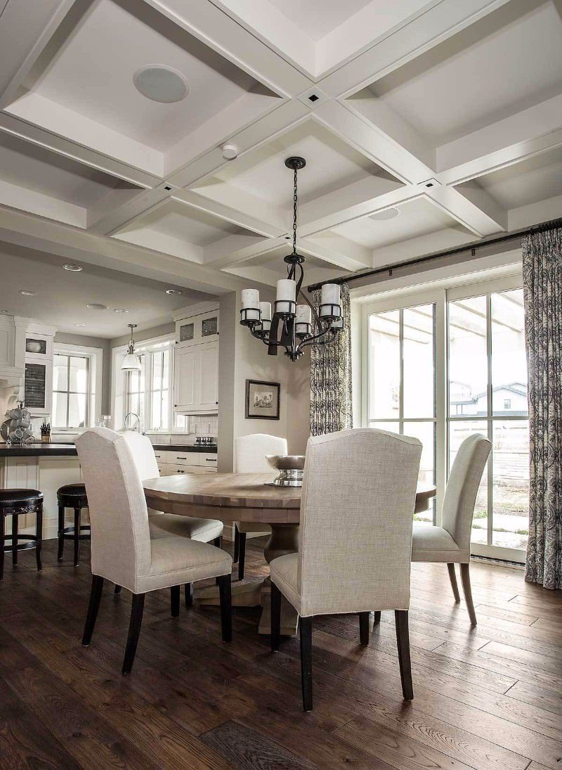 Classic dining room with coffered ceiling and full height glass windows covered with black draperies. It is lighted by a vintage chandelier that hung over a round dining table and gray highback chairs.