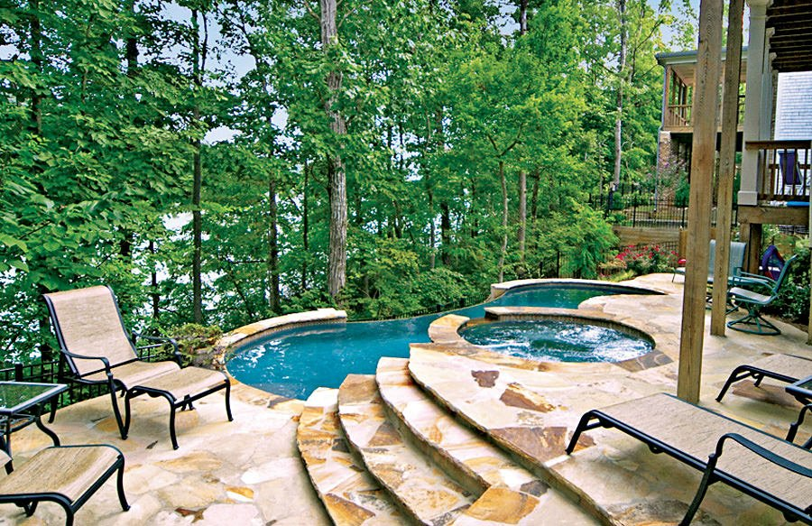 This home boasts a swimming pool with a jacuzzi surrounded by tall green trees.