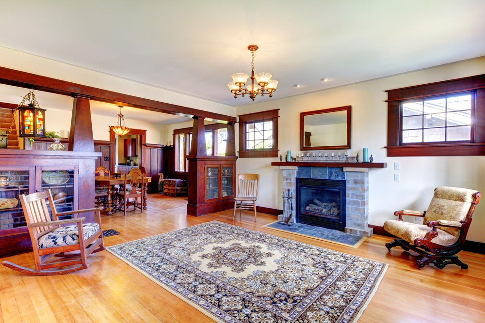 Craftsman-Style living room interior with a brick fireplace and an area rug in surrounded by rocking chairs.