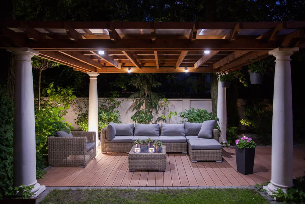 Glamorous deck featuring a rattan sofa set equipped with gray foam seats and backrests. The area is lighted by daylight bulbs while the greens and lovely plants provide refreshing look.