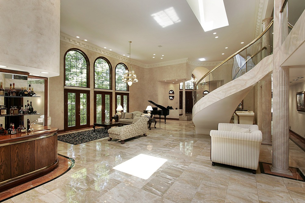 Large elegant foyer featuring sparkling tiles flooring mirroring the scattered recessed lights, chandelier and skylight. The staircase looks classy while the sofa set along with a rug and a center table look so gorgeous.
