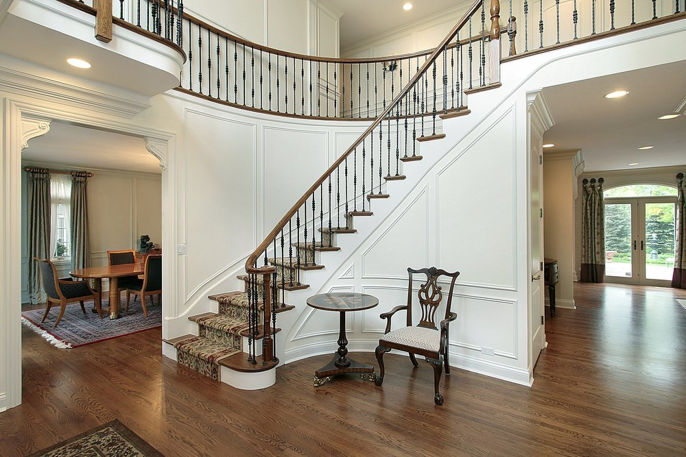 This foyer features a classy staircase with a rug, along with a chair and a side table.