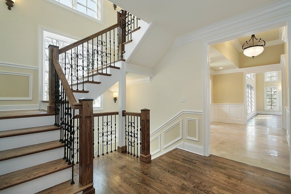 This second floor landing has a stylish hardwood flooring that leads to the home's hallway with a tiles flooring and a pendant lighting.
